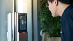 A man uses facial recognition technology to unlock a door.
